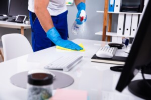 Man cleaning desk with spray and cloth